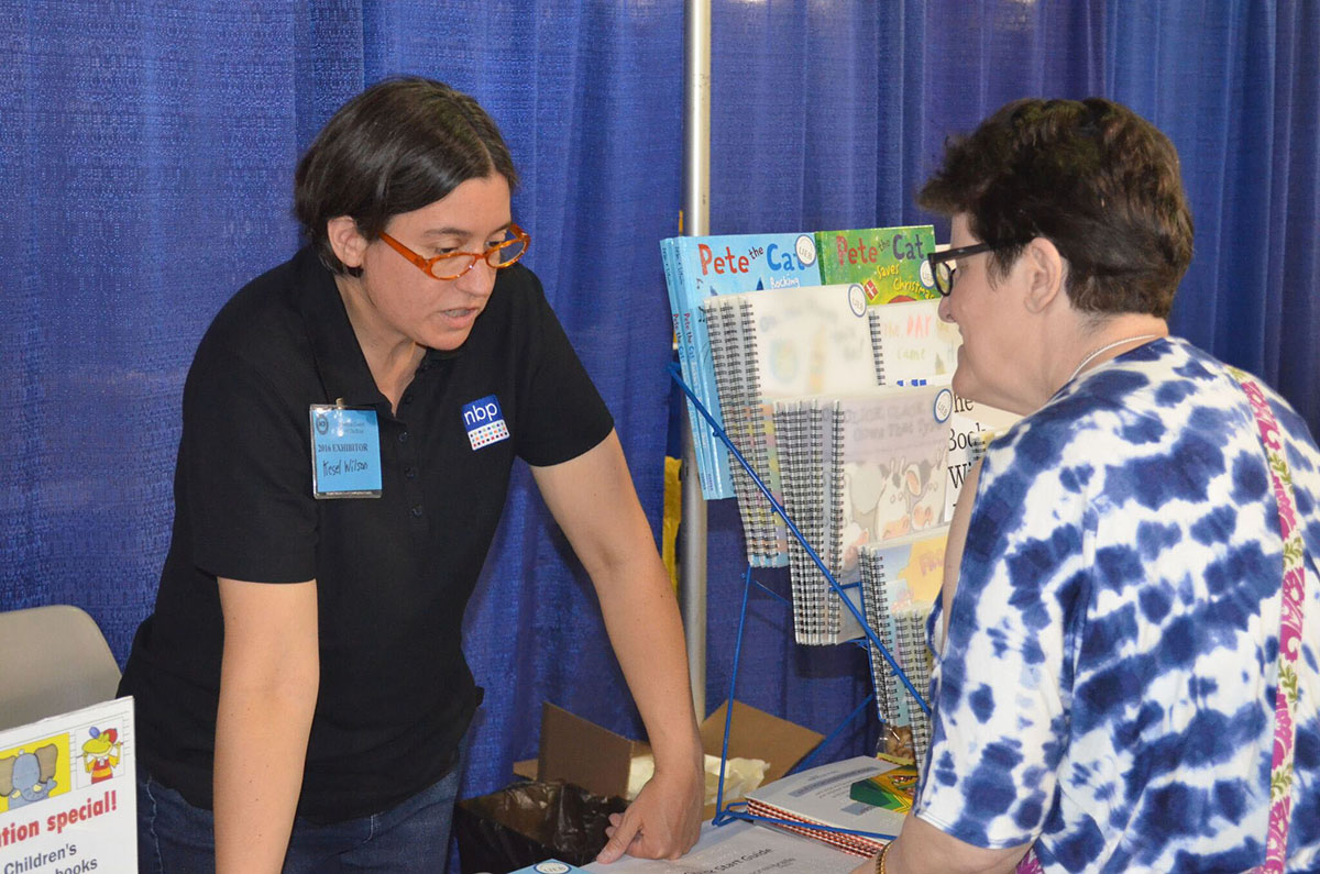 Exhibitor and attendee at convention exhibit booth